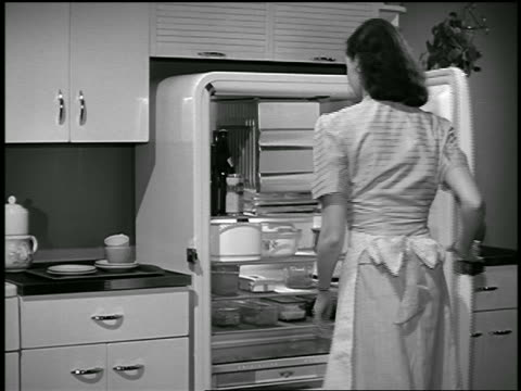 b/w 1943 housewife opening refrigerator / industrial - stay at home mother stock videos & royalty-free footage