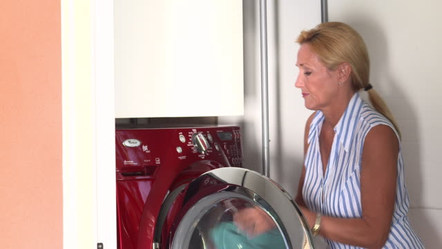 ws housewife places laundry into front loader washing machine and programming wash cycle  / rancho mirage, clifornia, united states - stereotypical housewife stock videos and b-roll footage