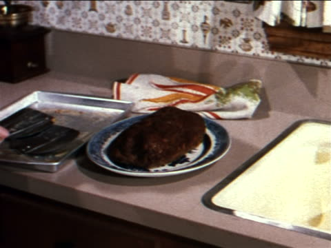 vídeos de stock, filmes e b-roll de 1962 housewife preparing meat loaf with tomato soup sauce for serving / industrial - comida salgada
