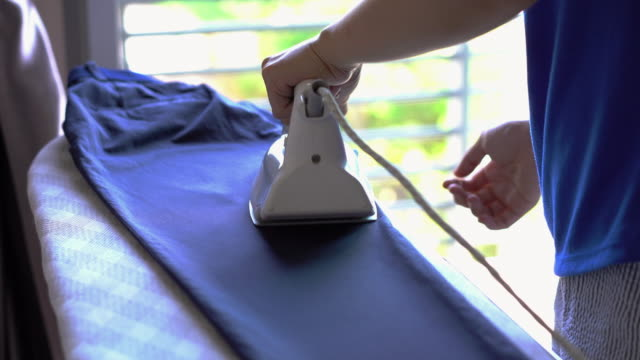housewife pressing iron. - iron appliance stock videos & royalty-free footage