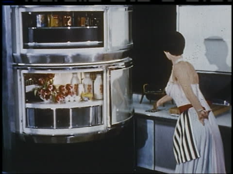 vidéos et rushes de 1956 housewife pushes button + food spins in circular, glass refrigerator in futuristic kitchen - 1956