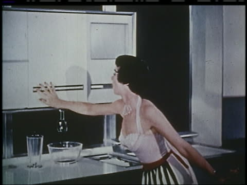 vidéos et rushes de 1956 housewife pushes buttons, mixer lowers from cabinet + starts in futuristic kitchen - 1956