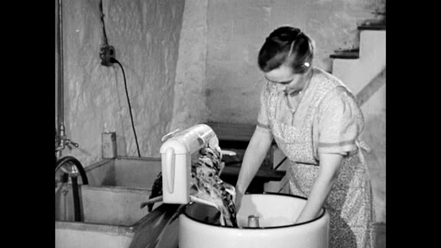 housewife puts clothes in electric washing machine and plugs it in / cu of agitator working / she goes upstairs to help daughter with ironing / goes... - housework stock videos and b-roll footage