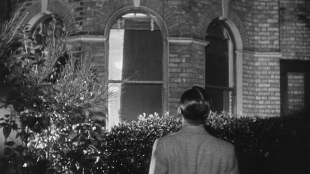 stockvideo's en b-roll-footage met 1939 montage housewife putting large cover over house window for blackout regulations, and husband outside guiding her during world war ii / united kingdom - stroomuitval