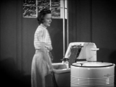 vidéos et rushes de b/w 1938 housewife putting wet clothes thru wringer in sink / turns + talks to camera / commerical - 1930
