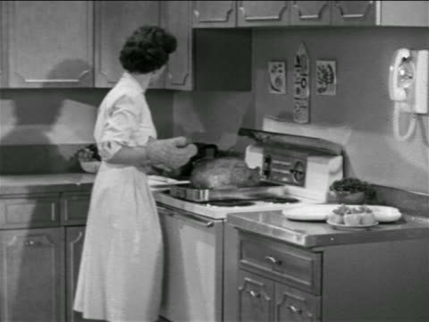 B/W 1957 housewife removing turkey from oven then answering telephone in kitchen / educational