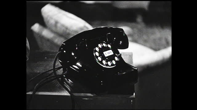 housewife sitting on the sofa while child crawls on the carpet in the living room; woman walks to the telephone while writing on notepad, talks to... - 1940 1949 stock videos & royalty-free footage