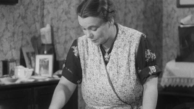 MONTAGE Housewife speaking with her working neighbor, then tending to dishes, her laundry, and her neighbor's laundry, while planning her workday, during World War II / United Kingdom