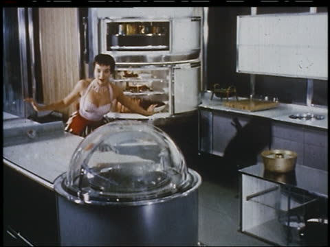 1956 housewife takes cake pan from cart + puts it in glass bubble oven in futuristic kitchen