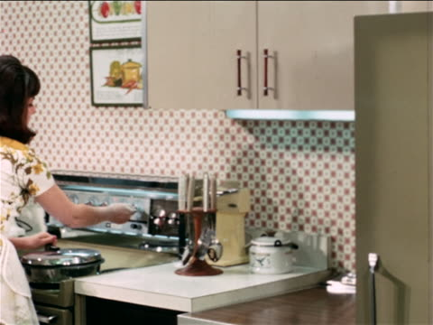 1968 rear view housewife unloading dishwasher in kitchen / industrial - anno 1968 video stock e b–roll