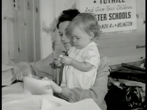 housewife w/ baby girl in arms, stuffing paper into envelopes. woman writing name & address on envelope. clerical, pamphlets, virginia, americana,... - ドキュメンタリー映画点の映像素材/bロール
