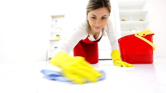 Housewife washing floors with a rag.
