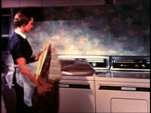 1958 housewife wearing apron loading clothes into washing machine