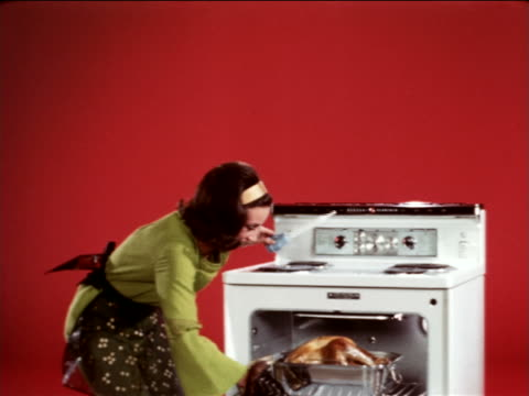 1967 housewife with brown hair opening oven + basting turkey in studio / industrial - ugnsstekt bildbanksvideor och videomaterial från bakom kulisserna