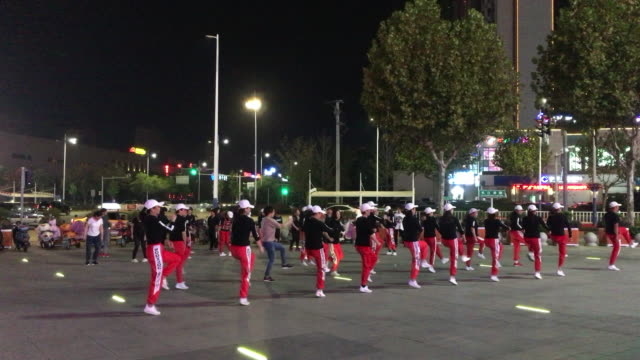 vídeos de stock e filmes b-roll de housewives are dancing on a square in front of a shopping mall at night. square dance, in china, are seen as a fitness exercise and collective... - dança quadrada