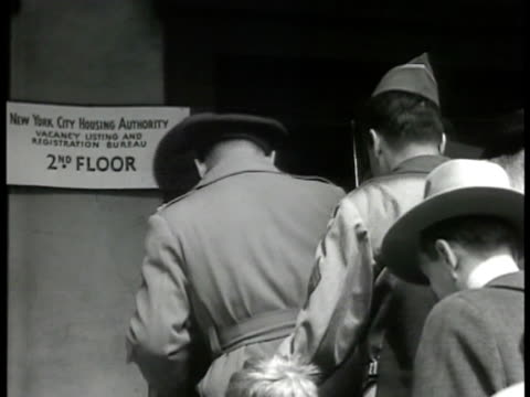 stockvideo's en b-roll-footage met housing authority building w/ people walking sidewalk elevated train bg people in line on housing authority steps int housing authority office w/... - 1946