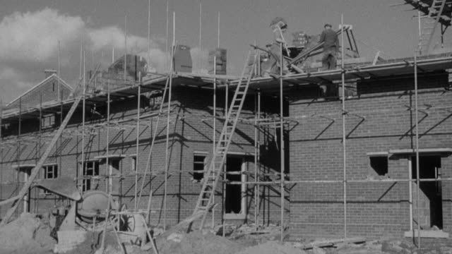 montage housing construction with bricklayer hauling bricks up ladder and across roof, pipe layer digging trench, and pouring concrete / united kingdom - brick stock videos & royalty-free footage