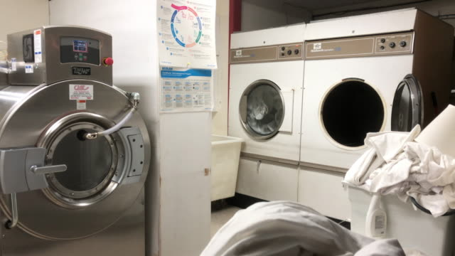 houston, texas, usa - november 2nd, 2019: washing machines are working in a laundromat, cleaning all the dirty hotel sheets. - コインランドリー点の映像素材/bロール