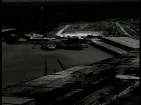 vidéos et rushes de houston waterfront seaport river ha xws docks cranes ha ws ships docked in channel ws ships in dock by building unloading houston ship channel port... - 1941