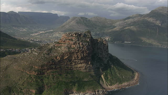 AERIAL Hout Bay with The Sentinel rock, Table Mountain in background, Cape Town, Western Cape, South Africa