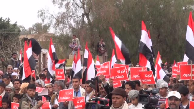 houthi supporters shout slogans and hold placards reading in arabic 'our revolution continues' during a rally commemorating the fifth anniversary of... - yemen stock videos & royalty-free footage