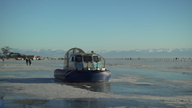 hovercraft moving on icy lake baikal against blue sky during winter - hovercraft stock videos & royalty-free footage