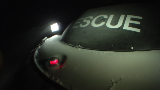 A hovercraft provides searchlights for rescuers in a blizzard.
