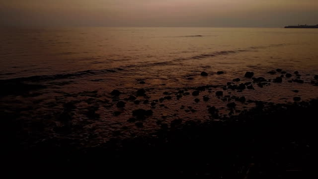 Zweefde Over rotsachtig strand na zonsondergang