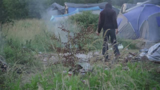 how muslim migrants at calais cope with ramadan ext various views of the jungle where migrants trying to cross to britain live migrants sitting on... - calais stock videos and b-roll footage
