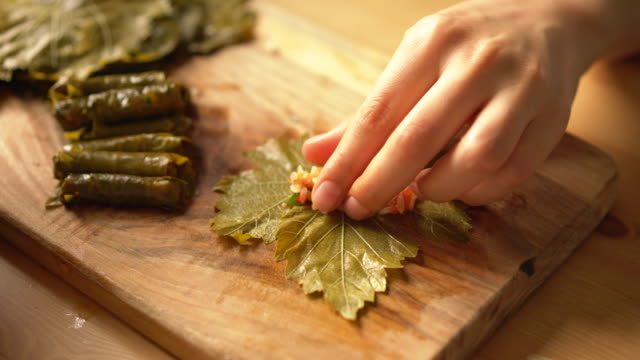 how to make homemade turkish traditional dish stuffed grape leaves with olive oil - stuffing grape leaves - vegetarian meal stock videos & royalty-free footage