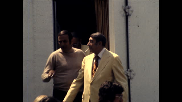 howard cosell emerges from a trailer with a cigarette in his mouth. there is a tv camera on top of the trailer. a woman takes photos with her 35mm... - robert goulet stock videos & royalty-free footage