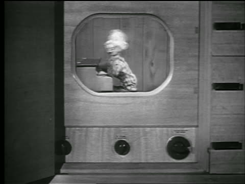 vídeos de stock, filmes e b-roll de b/w 1948 tv set howdy doody playing piano + waving to viewers / howdy doody - marionete brinquedo