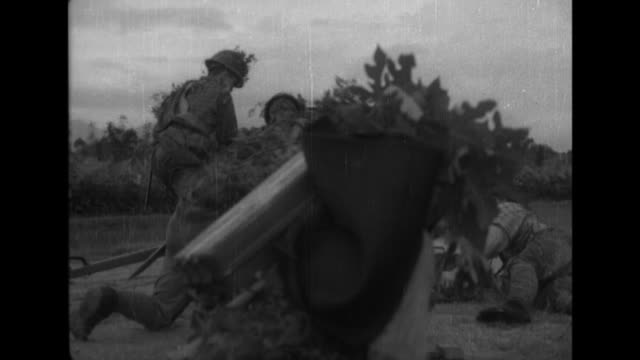 Howitzers soften up the enemy before Imperial Japanese Army infantrymen assault the enemy across rice paddies