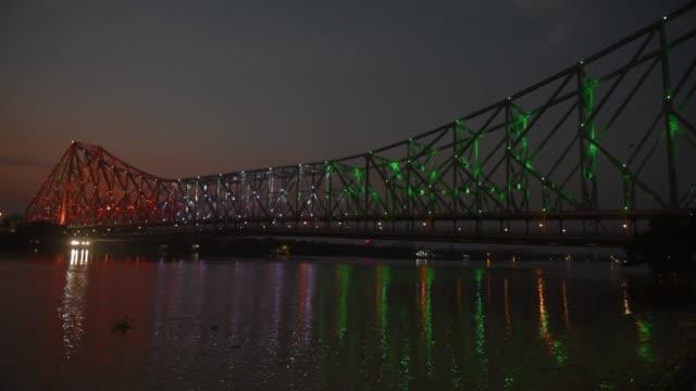howrah bridge illuminated with the indian national flag colours to honour the 'frontline warriors' of the covid-19 coronavirus. in kolkata, india, 11... - howrah bridge stock videos & royalty-free footage