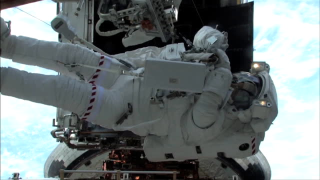 hubble space telescope orbiting earth / astronauts floating outside hubble making repairs on sts125 mission 4 to repair the telescope / astronaut... - sternenteleskop stock-videos und b-roll-filmmaterial