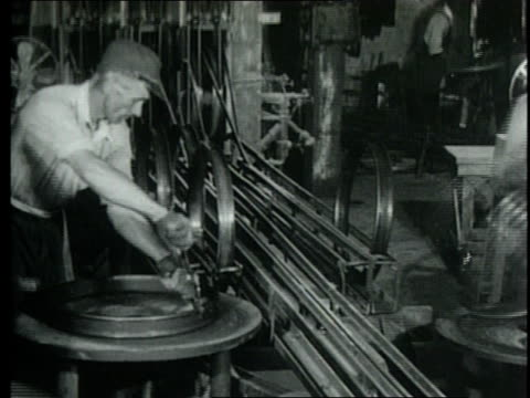 stockvideo's en b-roll-footage met 1952 montage hubcaps and other automobile parts are transported to ford assembly line for installation / detroit, michigan, united states - assemblagelijn