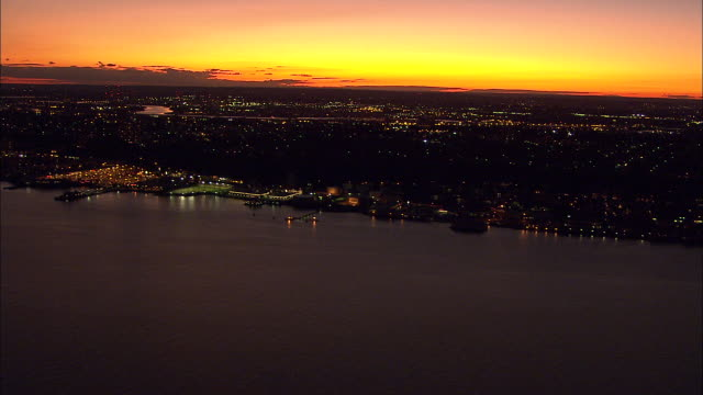over hudson river lower frame new jersey cityscape w/ lights on yellow orange sky bg nyc nj - orange new jersey stock videos & royalty-free footage