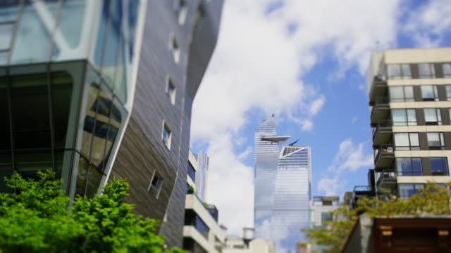 hudson yards high-rise buildings stand among the midtown manhattan buildings along the high line park under the blue sky in spring season at new york city ny usa on may 15 2019. - chelsea manhattan video stock e b–roll