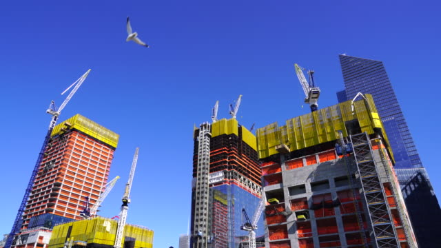 hudson yards redevelopment project is progressing at west midtown manhattan day by day on mar. 23 2017. many construction cranes work on the growing structures. - クレーン点の映像素材/bロール