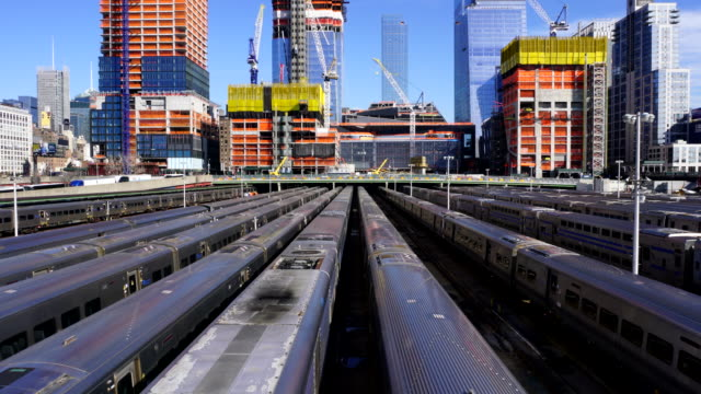 Hudson Yards Redevelopment Project is progressing at West Midtown Manhattan day by day on Apr. 05 2017. Camera captures rows of trains at Hudson Rail Yards. Many construction cranes work on the growing structures.