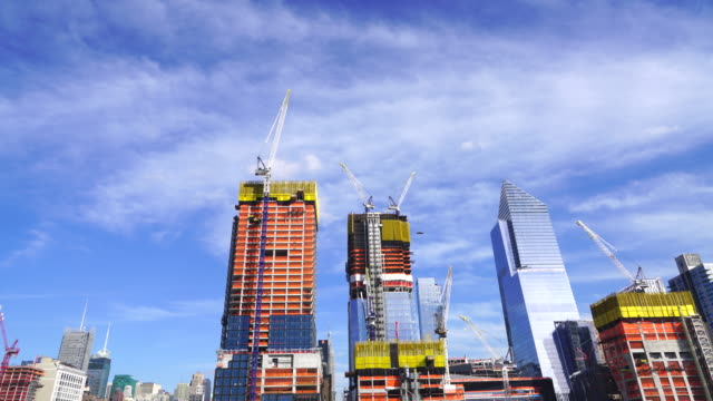 Hudson Yards Redevelopment Project is progressing at West Midtown Manhattan day by day on Apr. 05 2017. Camera captures moving clouds over the Hudson Yards construction site. Many construction cranes work on the growing structures.