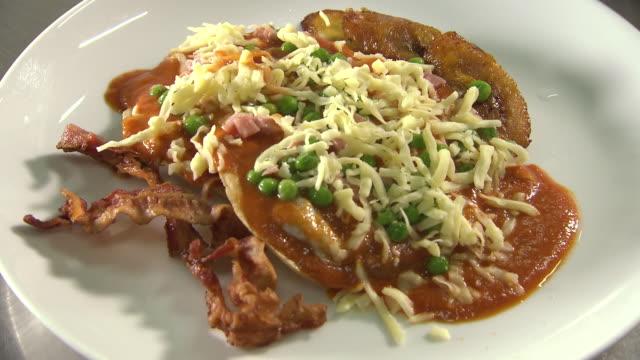 vídeos de stock, filmes e b-roll de huevos motuleños served onto a plate, mexico - banana de são tomé