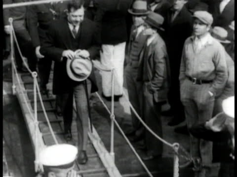 huey long in dress colthing walking onto german cruiser emden shaking hands w/ commander of emden sailors loading firing salute w/ artillery - anno 1930 video stock e b–roll
