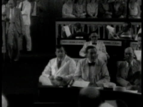 huey long standing w/ elder male holding newspaper. huey long in white suit sitting in government building w/ others wiping face w/ cloth. - 1932 stock videos & royalty-free footage