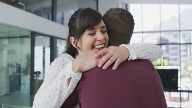 a hug can make anywhere feel like home - coworker stock videos & royalty-free footage