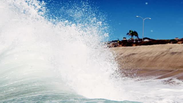 vídeos de stock, filmes e b-roll de enorme retrolavagem e onda quebrando no verão de areia dourada da califórnia com palmeiras ao fundo. foto em slowmo no red dragão no 300fps. - deep sea diving