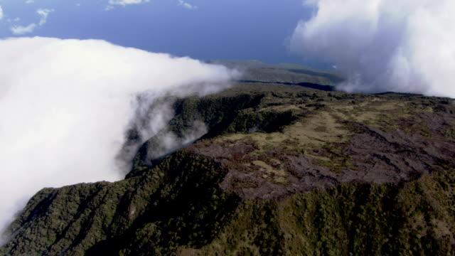 huge banks of clouds settle over a mountain plateau. - altopiano video stock e b–roll