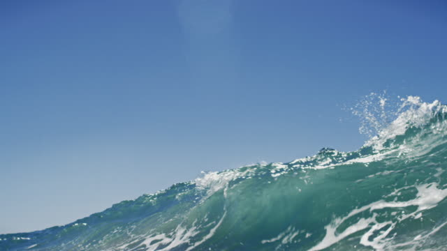Huge beautiful wave POV as wave breaks over camera on shallow sand beach in the California summer sun. Shot in slowmo.