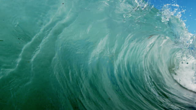 Huge beautiful wave POV as wave breaks over camera on shallow sand beach in the California summer sun. Shot in slowmo on the Red Dragon at 300FPS.