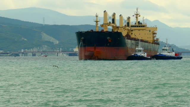 riesiges Frachtschiff betritt den Port mit Hilfe von Schleppern